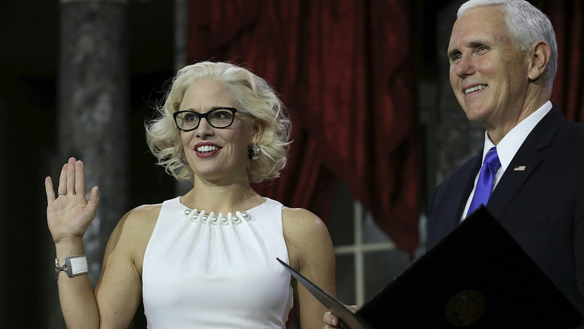 U.S. Sen. Kyrsten Sinema holds a lawbook as she is sworn in by Vice President Mike Pence during the swearing-in re-enactments for recently elected senators in the Old Senate Chamber on Capitol Hill in Washington, D.C., Jan. 3, 2019.