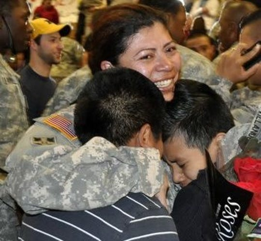 Marta Villanueva served in the U.S. Army and earned GI Bill benefits to attend college. In this photo, Villanueva's twin sons embrace her after she returned home from Iraq in 2011.