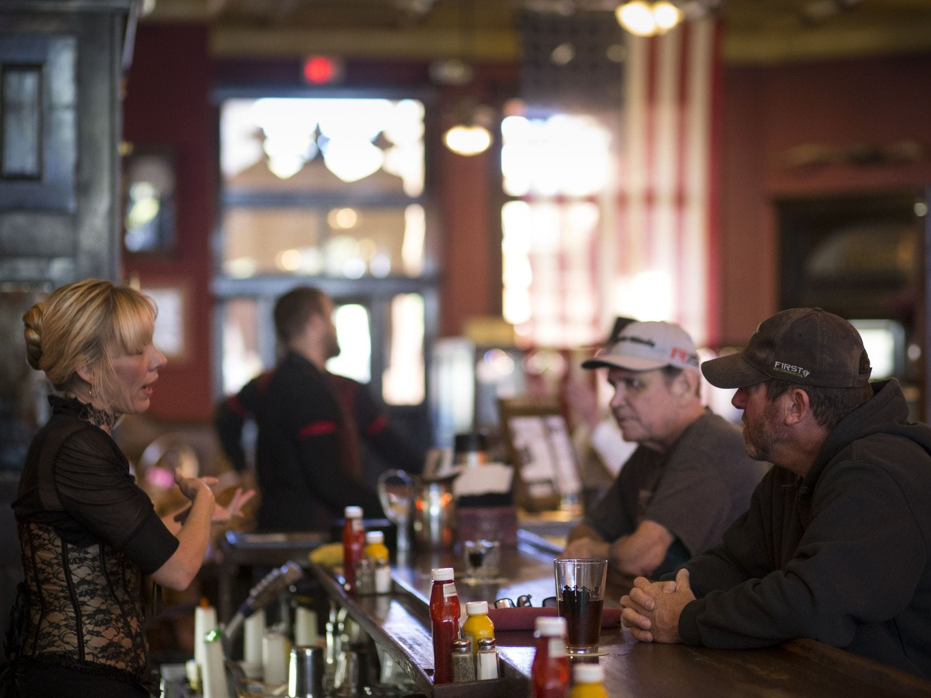 Martha Mekeel (izq) habla con los clientes, Bob Johnson (der) y Larry Hadley (centro), el 6 de noviembre de 2017, en Palace Saloon y Restaurant 120 S. Montezuma Street, Prescott, Arizona.