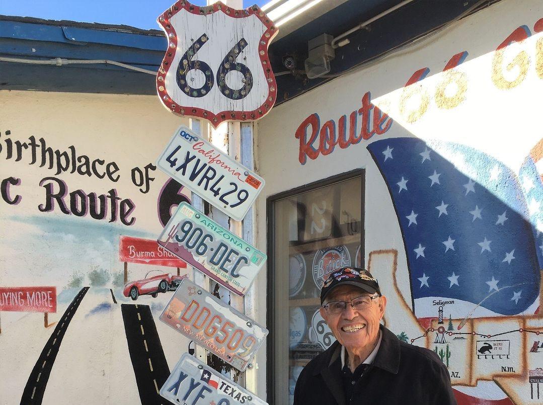 Las placas donadas a lo largo de los años adornan un poste indicador de la Ruta 66 en las afueras de la tienda de regalos de la familia Angel Delgadillo en Seligman.