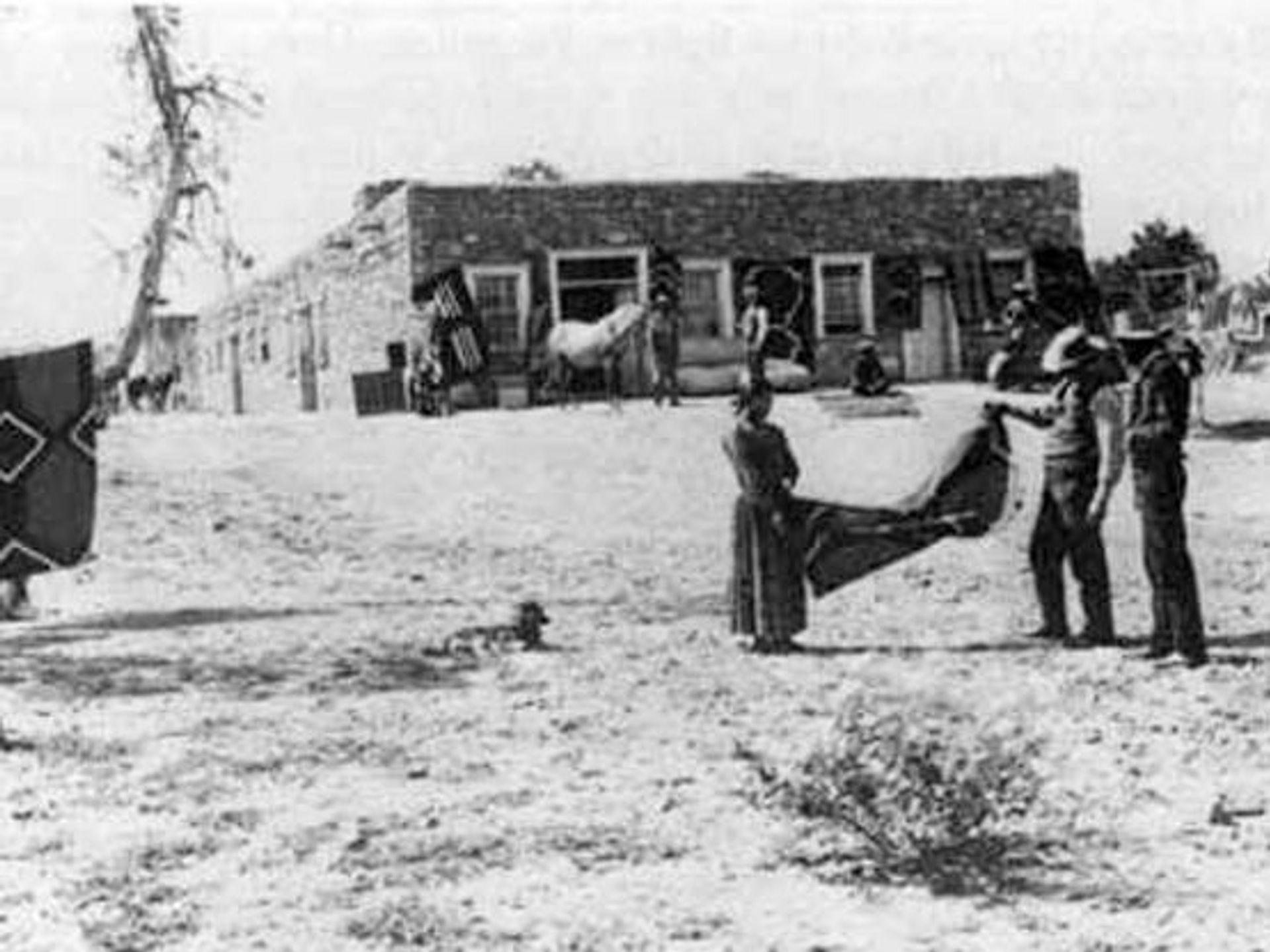 John Lorenzo Hubbell, sostiene un extremo de una alfombra, en el puesto comercial de Hubbell en la década de 1890.
