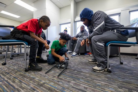 SC4 basketball player Tariq Hardy, right, watches STEAM Academy at Woodrow Wilson fifth-graders Jamil Brown, center, and Parijean Martin fix a robot they constructed in class Wednesday, Dec. 19, 2018 in a classroom at the school.