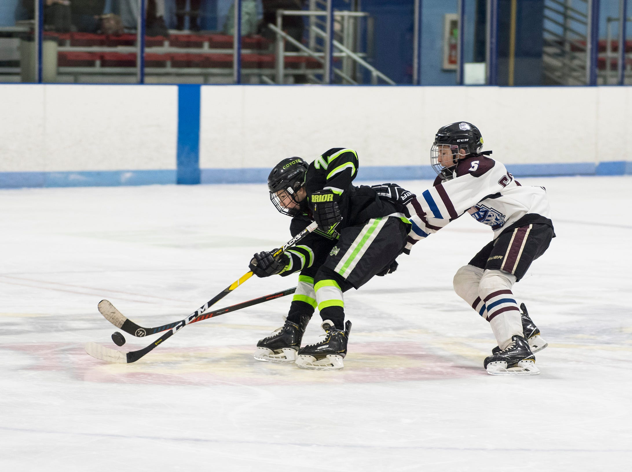 Huron Perth Lakers defenseman Luke Bogart (5) hits the puck away from Chicago Mission defenseman Michael Phelan during their Silver Stick Finals PAAA-B match Thursday, Jan. 3, 2019 at Glacier Pointe Ice Complex.