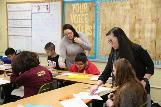 From left, Christina Corgi and Cara Braun work with students in her 7th grade social studies class at La Grange Middle School on January 3, 2019.