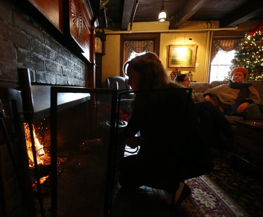 Front desk agent Madison Anthony tends to the fireplace in the lobby of the Beekman Arms in Rhinebeck on December 27, 2018.