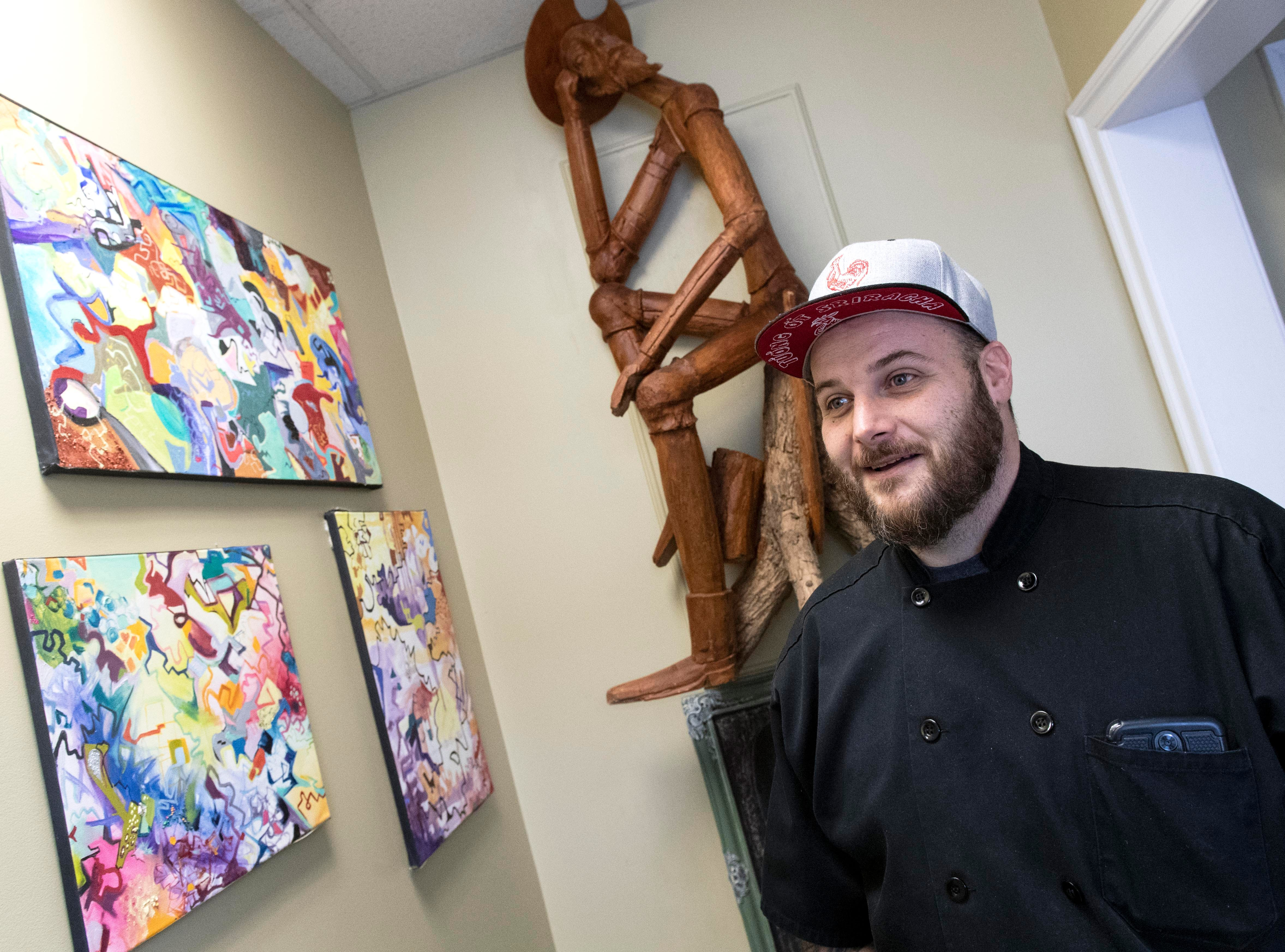 Michael Monigle, owner and executive chef at HomeGrown Catering in the Frey Mansion, talks about the artwork while standing in the front entrance of the restaurant, Thursday, Jan. 3, 2019. The restaurant is set to open on Jan. 10, with an American-style menu with a French twist. It's also BYOB.