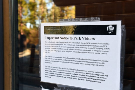 A laminated sign taped to the shuttered entry booth is all that greets visitors to Yosemite National Park at its Big Oak Flat entrance off Highway 120. Though the park is open, the ongoing government shutdown has limited park operations.