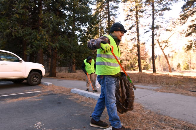 Anthony Martinez, 42, and Jessica Garcia, 29, pick up trash along the main road into Yosemite Valley on Jan. 2, 2019. Martinez and Garcia both spent their days off from work at nearby Tenaya Lodge to pick up trash inside Yosemite during the 2018/19 government shutdown.