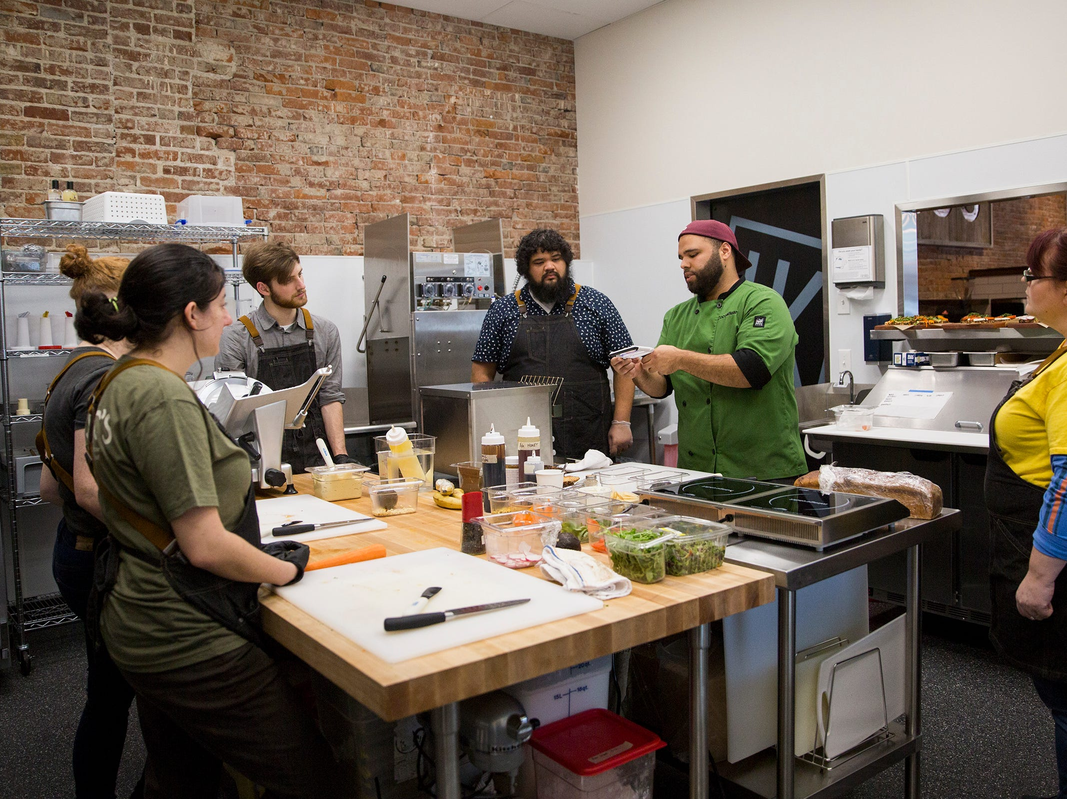 Jonathan Jones (center) shows Isaac's Downtown employees how to make certain toast items on the menu in Salem on Thursday, Jan. 3, 2019. Jones created the menu.