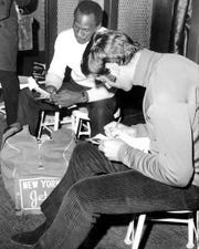 Joe Namath autographing pictures while Earl Christy reads his fan mail before they get ready to leave for Miami Florida to meet Baltimore for the Super Bowl on January 12.