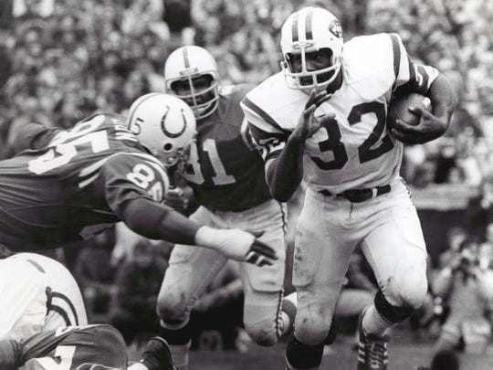 New York Jets running back Emerson Boozer (32) is pursued by Baltimore Colts defensive end Roy Hilton (85) and Billy Newsome (81) at Memorial Stadium.