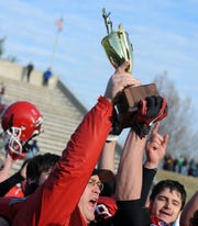 Head Coach Robert Casto holds up the championship trophy as he presents it to his team after it is awarded to the Riverheads High School varsity football team following their winning the Group A, Division I  Championship in Salem on Saturday, Dec. 11, 2010.