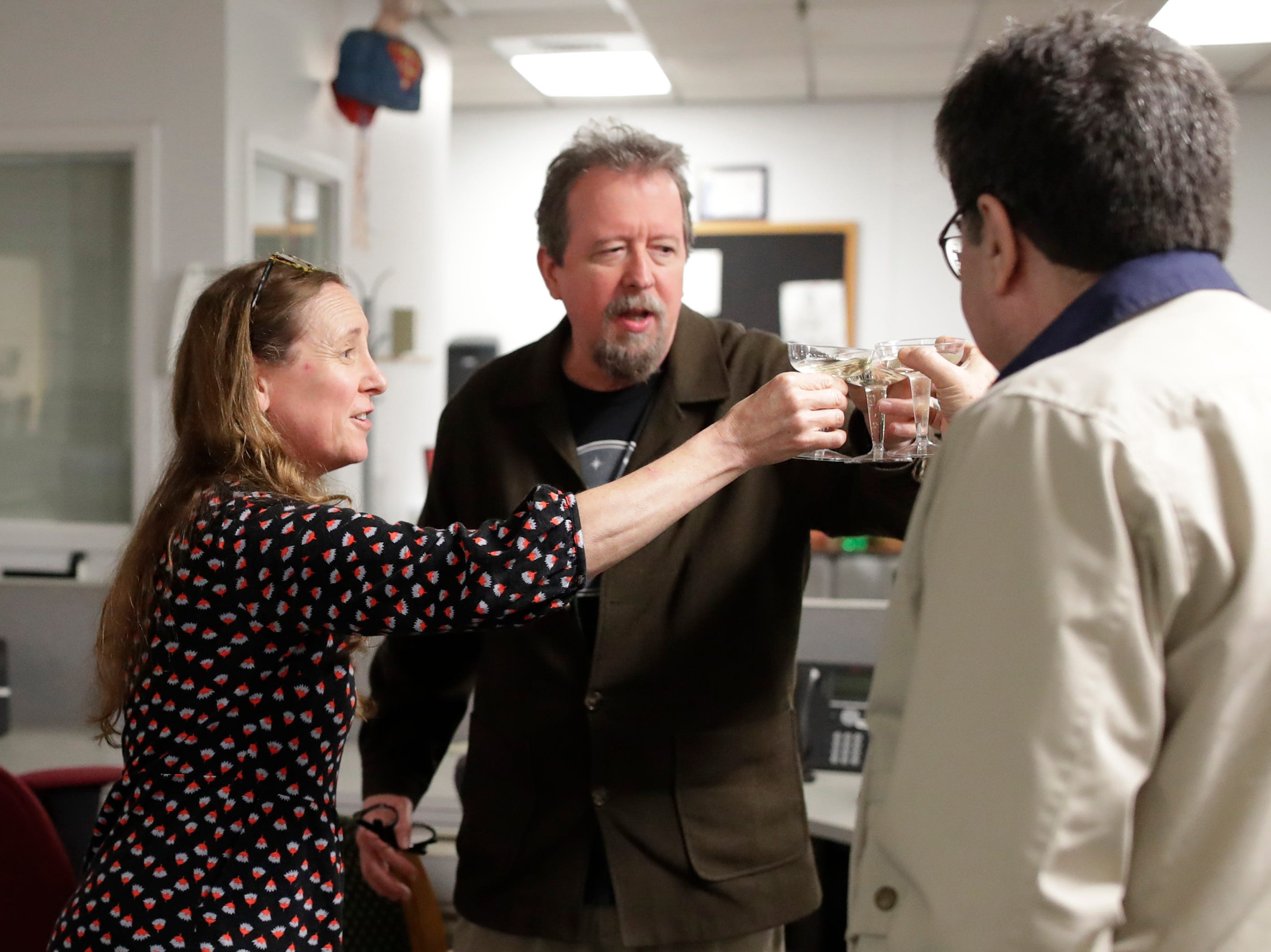 News Director Jennifer Portman, Former Arts and Entertainment Editor Mark Hinson and Capitol Reporter James Call toast to Hinson on his last day of work at the Tallahassee Democrat Wednesday, Jan. 2, 2019.