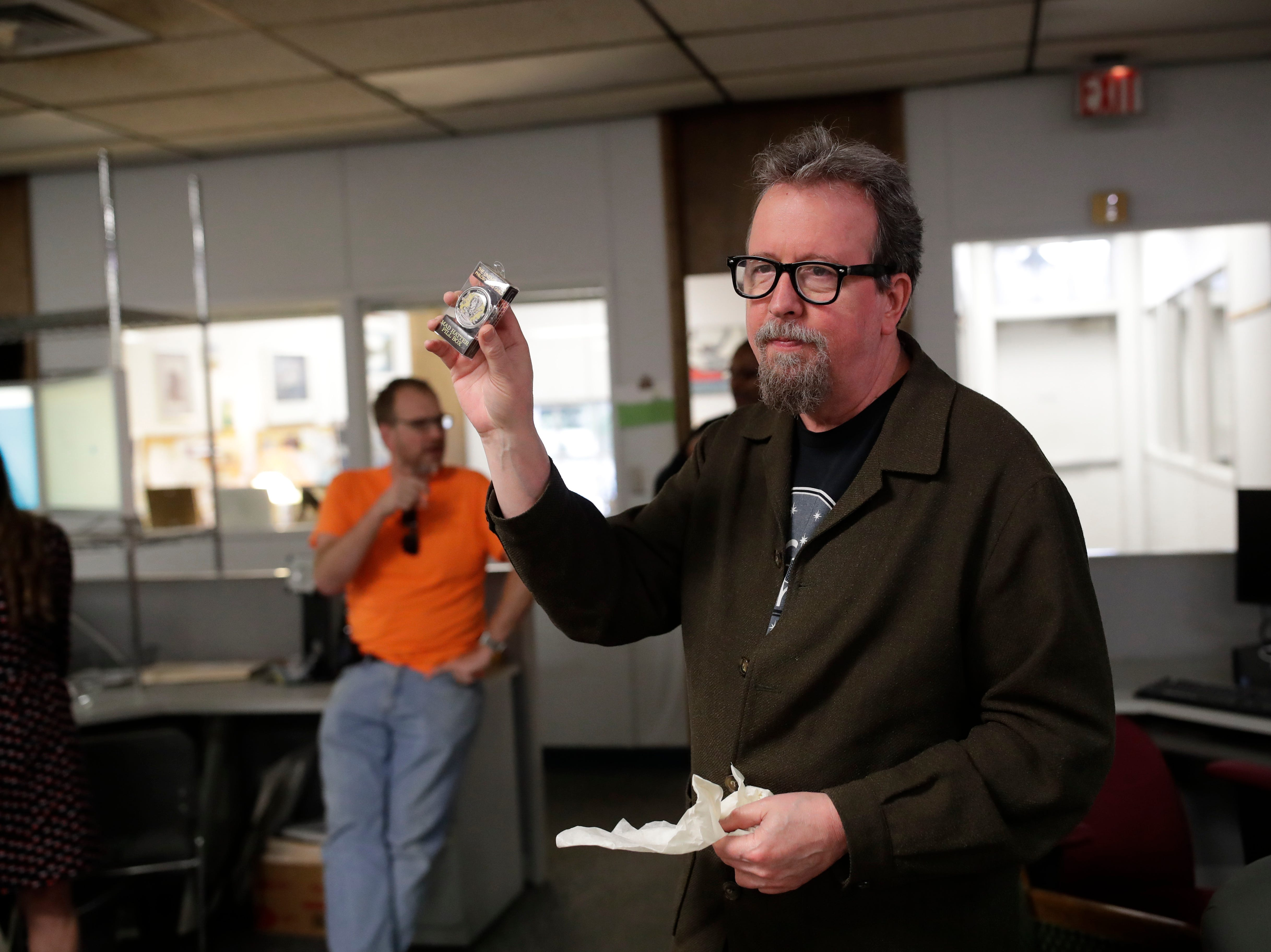 Former Arts and Entertainment Editor Mark Hinson opens gifts from his colleagues on his last day of work at the Tallahassee Democrat Wednesday, Jan. 2, 2019.