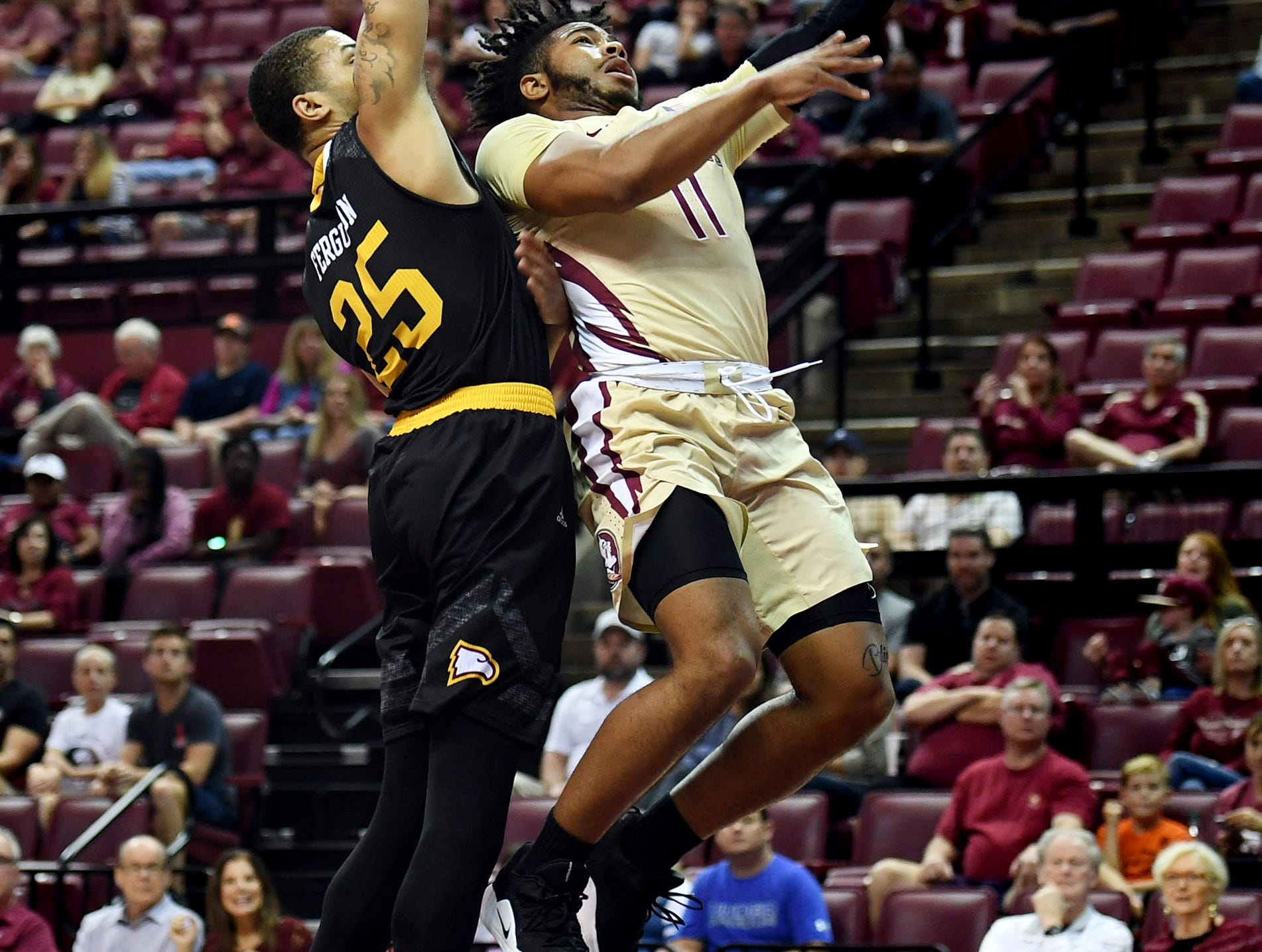 Jan 1, 2019; Tallahassee, FL, USA; Florida State Seminoles guard David Nichols (11) shoots the ball past Winthrop Eagles forward Josh Ferguson (25) during the first half at Donald L. Tucker Center. Mandatory Credit: Melina Myers-USA TODAY Sports