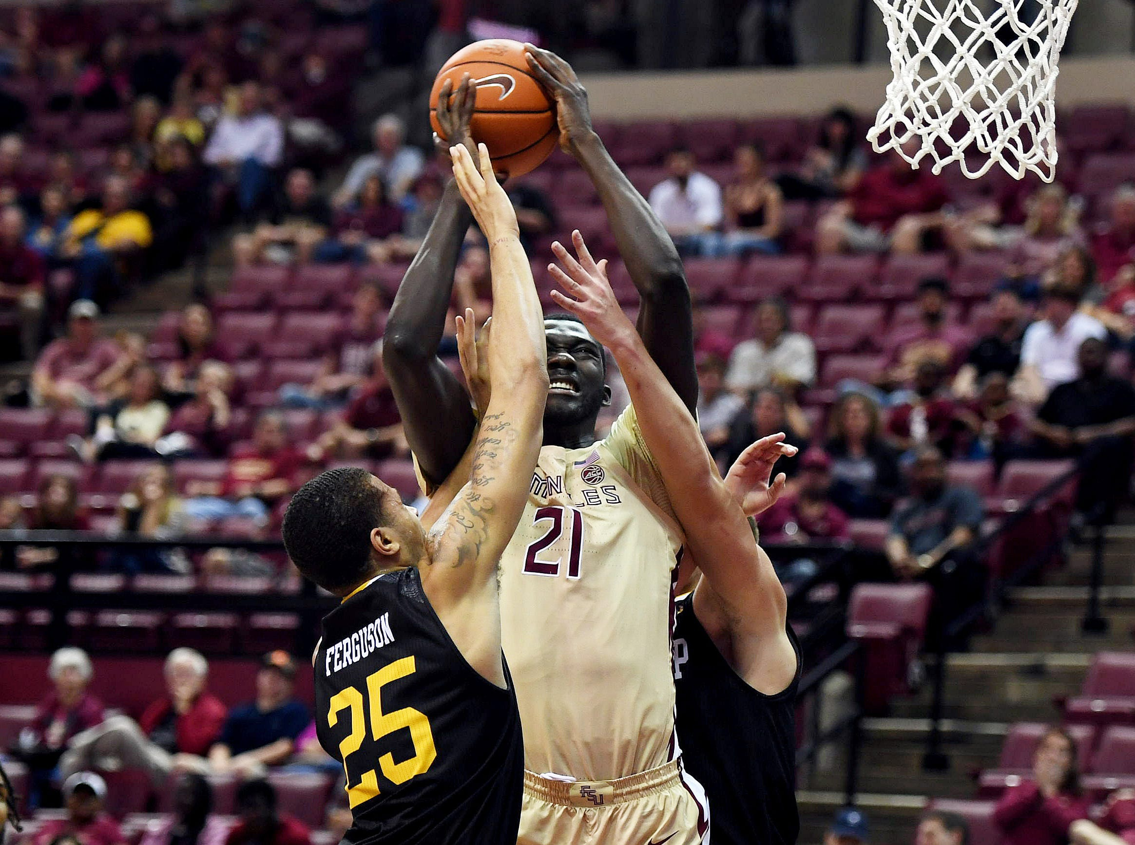 Jan 1, 2019; Tallahassee, FL, USA; Florida State Seminoles center Christ Koumadje (21) controls the ball as ball Winthrop Eagles forward Josh Ferguson (25) defends during the first half at Donald L. Tucker Center. Mandatory Credit: Melina Myers-USA TODAY Sports