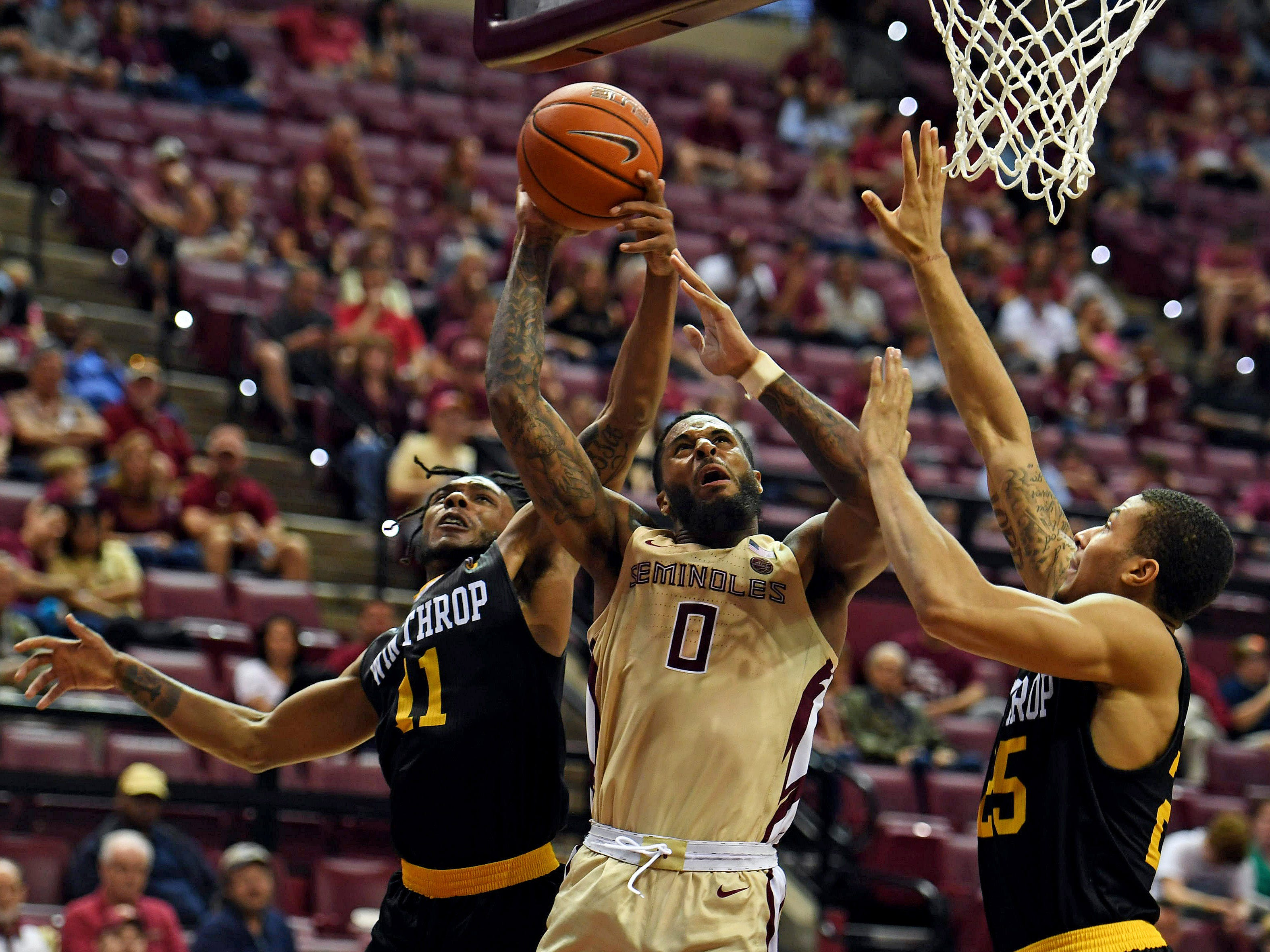 Jan 1, 2019; Tallahassee, FL, USA; Florida State Seminoles forward Phil Cofer (0) goes for a basket past Winthrop Eagles guard Charles Falden (11) during the game at Donald L. Tucker Center. Mandatory Credit: Melina Myers-USA TODAY Sports