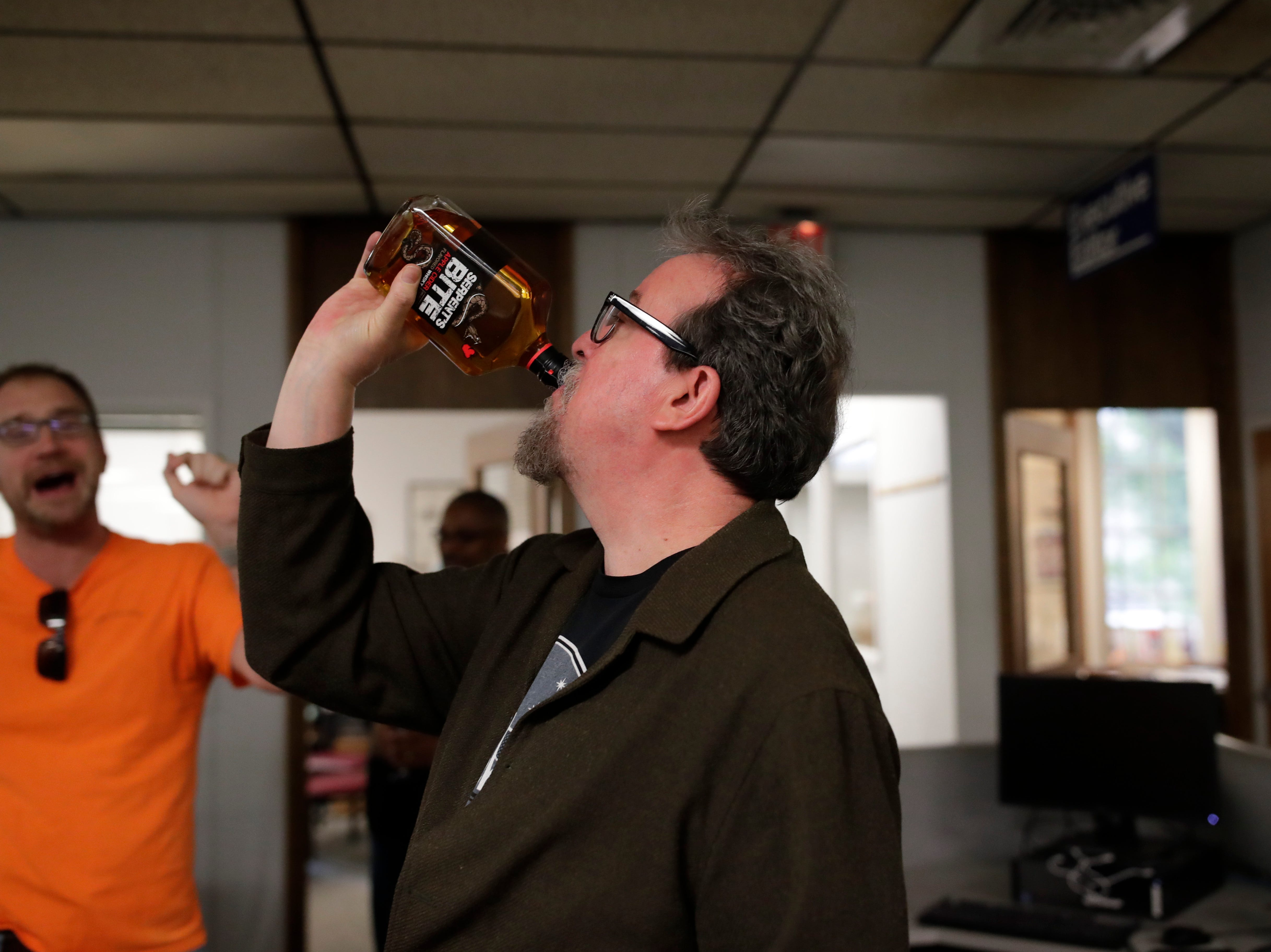 Former Arts and Entertainment Editor Mark Hinson pretends to take a swig from a bottle of whiskey presented to him by Executive Editor William Hatfield on Hinson's last day of work at the Tallahassee Democrat Wednesday, Jan. 2, 2019.