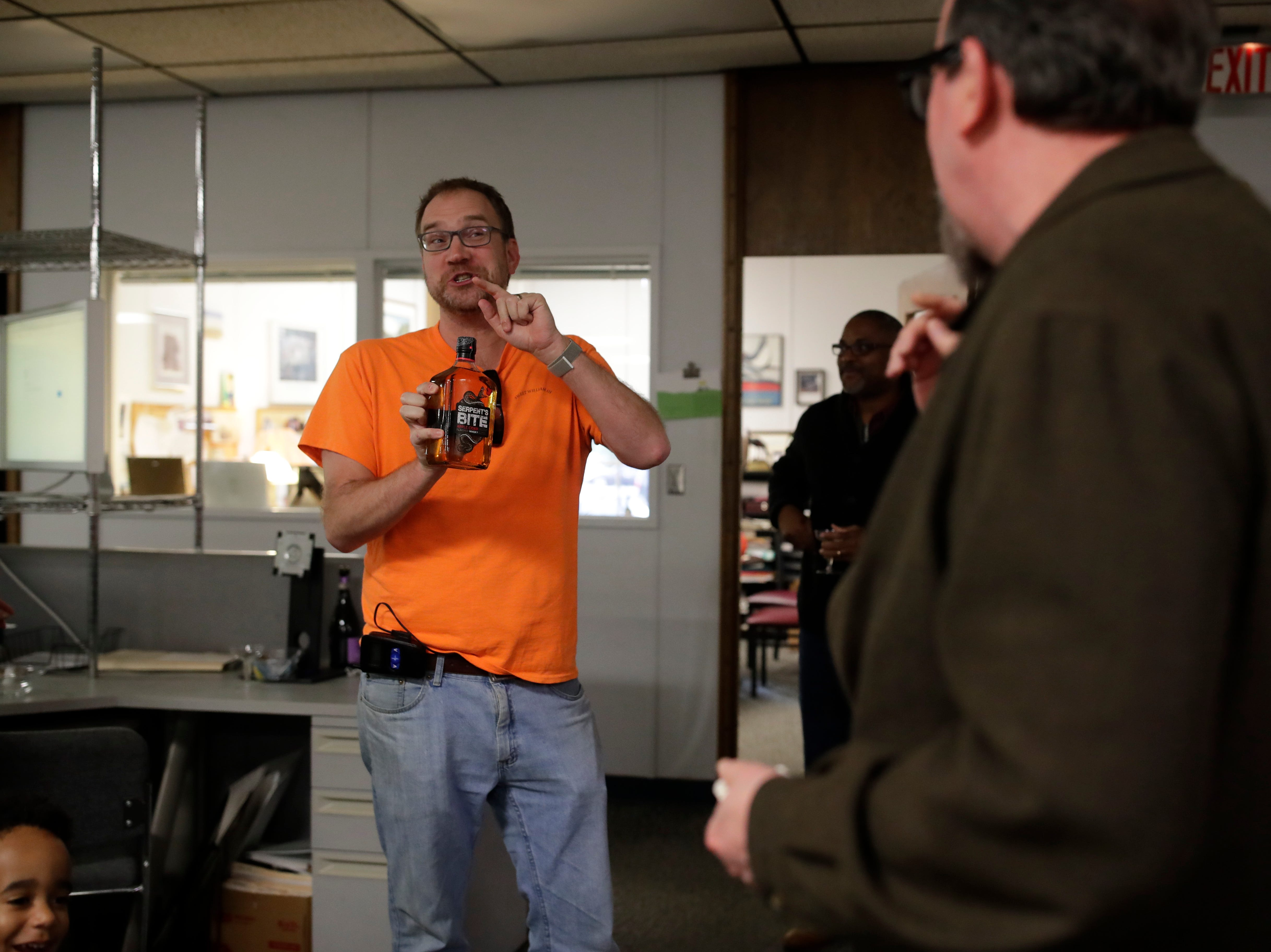 Executive Editor William Hatfield presents Former Arts and Entertainment Editor Mark Hinson with a bottle of whiskey on his last day of work at the Tallahassee Democrat Wednesday, Jan. 2, 2019.