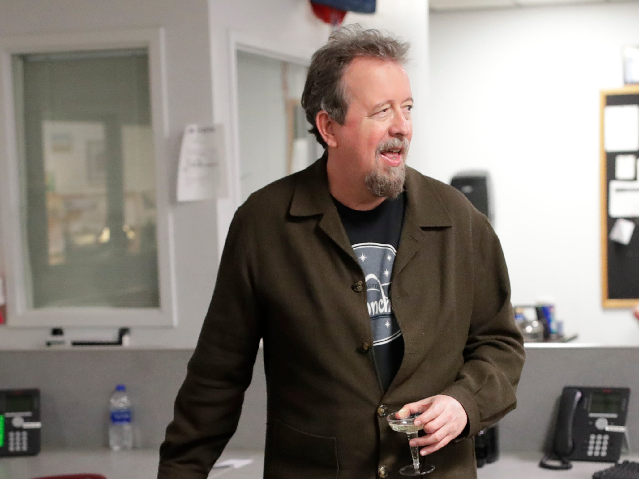 Former Arts and Entertainment Editor Mark Hinson holds a glass of Prosecco as his colleagues gather around to say goodbye to him on his last day of work at the Tallahassee Democrat Wednesday, Jan. 2, 2019.