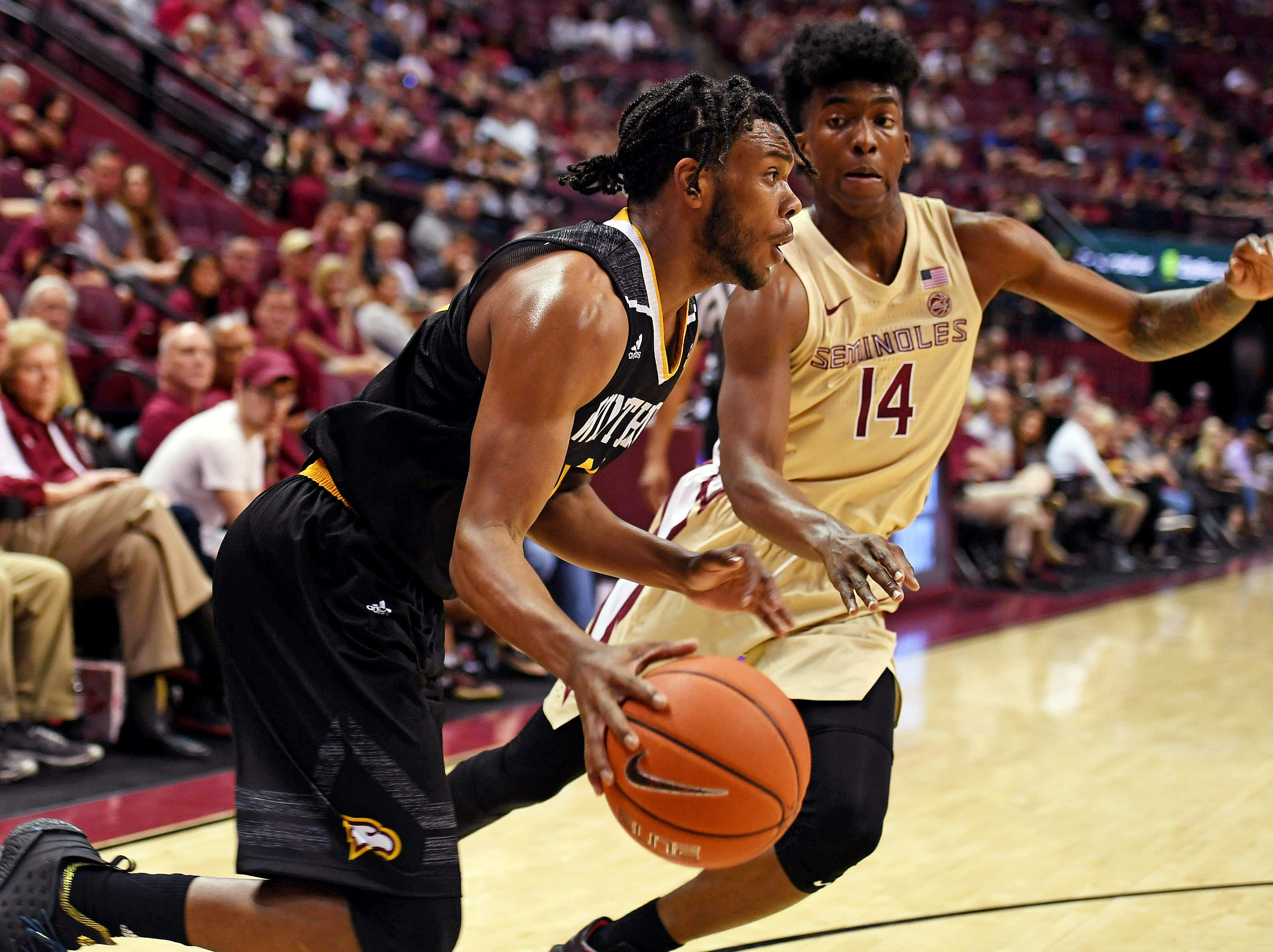 Jan 1, 2019; Tallahassee, FL, USA; Winthrop Eagles guard Charles Falden (11) dribbles the ball as Florida State Seminoles guard Terance Mann (14) defends during the first half at Donald L. Tucker Center. Mandatory Credit: Melina Myers-USA TODAY Sports