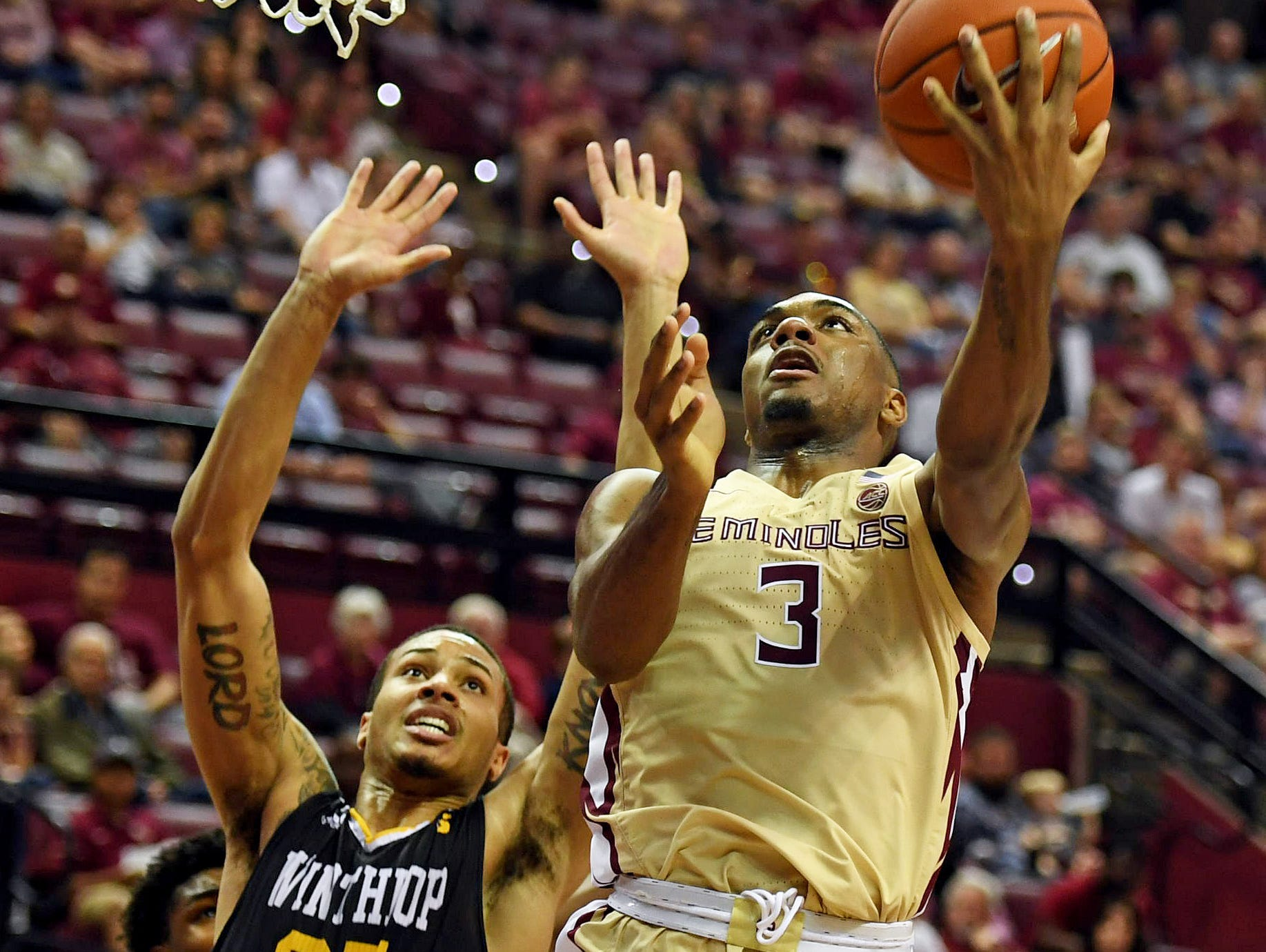 Jan 1, 2019; Tallahassee, FL, USA; Florida State Seminoles guard Trent Forrest (3) shoots the ball past past Winthrop Eagles forward Josh Ferguson (25) during the game at Donald L. Tucker Center. Mandatory Credit: Melina Myers-USA TODAY Sports