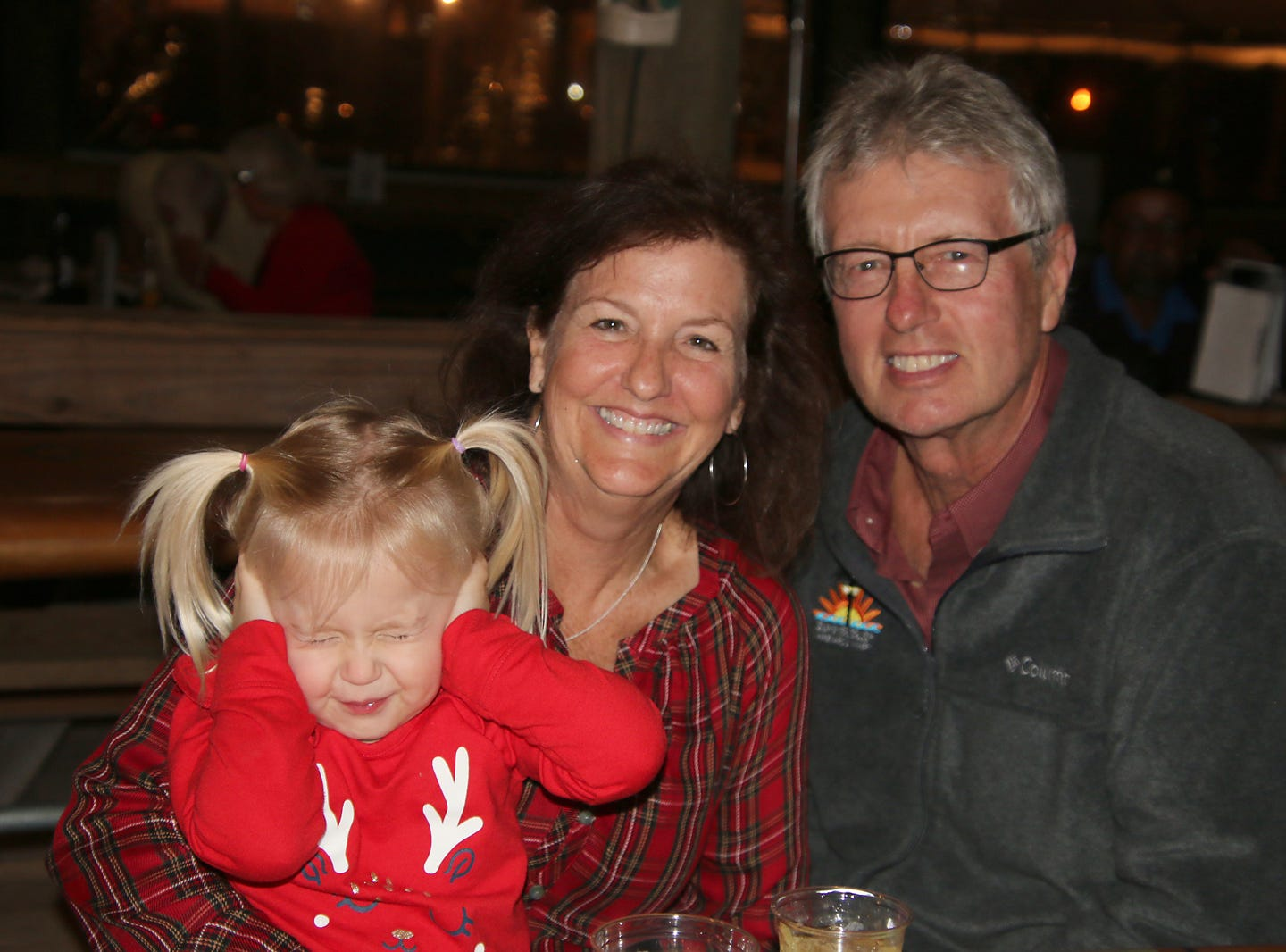Summer Crush owners Gary and Susan Roberts and their granddaughter, who wasn't quite sure about the music, at the Fort Pierce Jazz &Blues Society's Ring-a-Ding-Ding Holiday Fling at Summer Crush Vineyard & Winery.