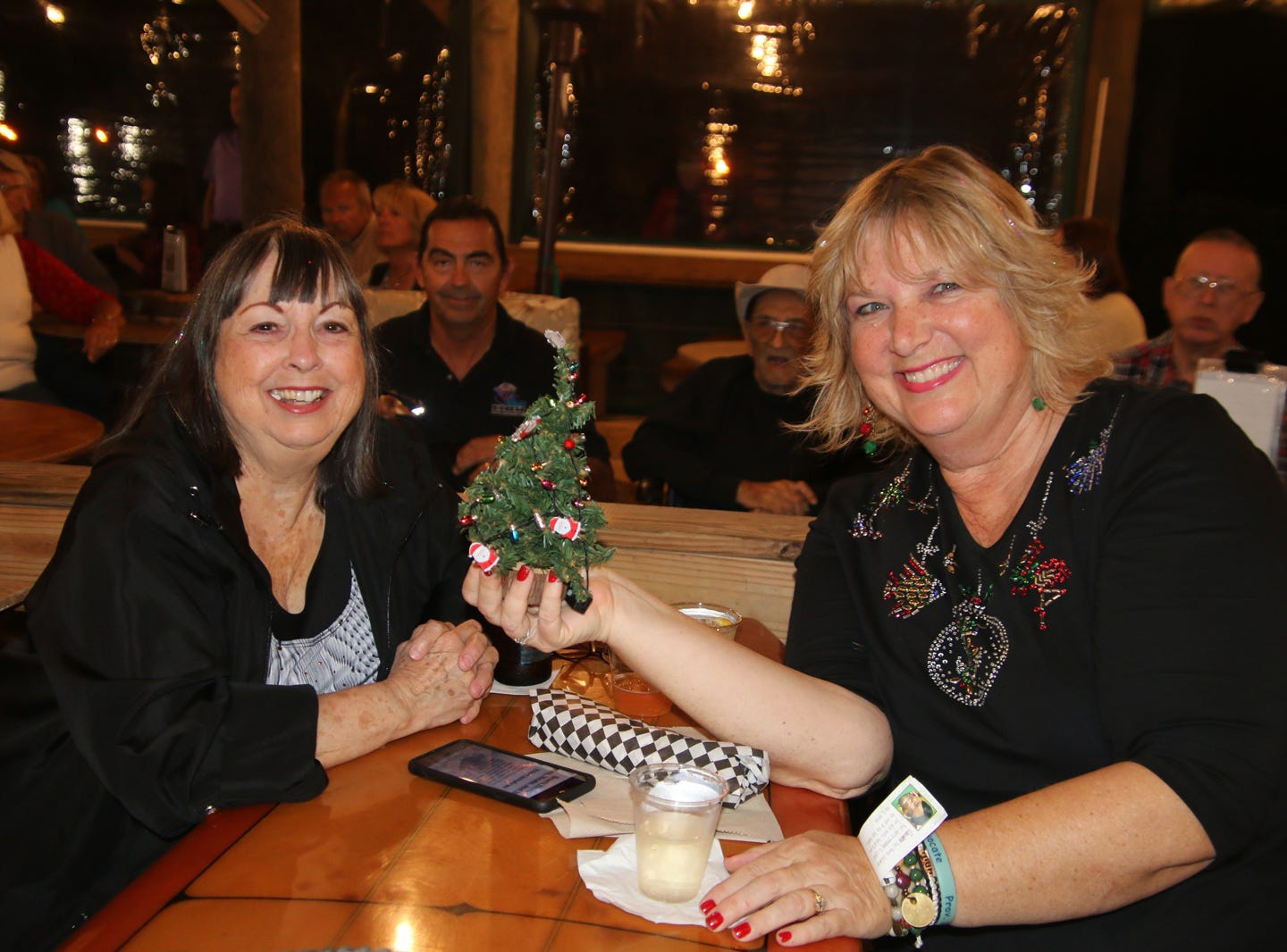 Patty Durham, left, and Elisa Groendyke celebrate the season at the Fort Pierce Jazz &Blues Society's  Ring-a-Ding-Ding Holiday Fling at Summer Crush Vineyard & Winery.
