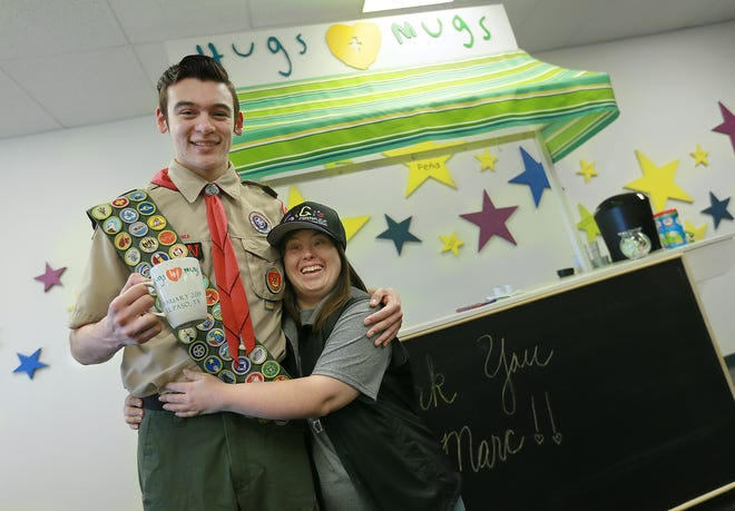 Eagle Scout candidate Marc Pacheco gets a hug from Melissa Moody during the unveiling of his project Thursday at Gigi's Playhouse.
