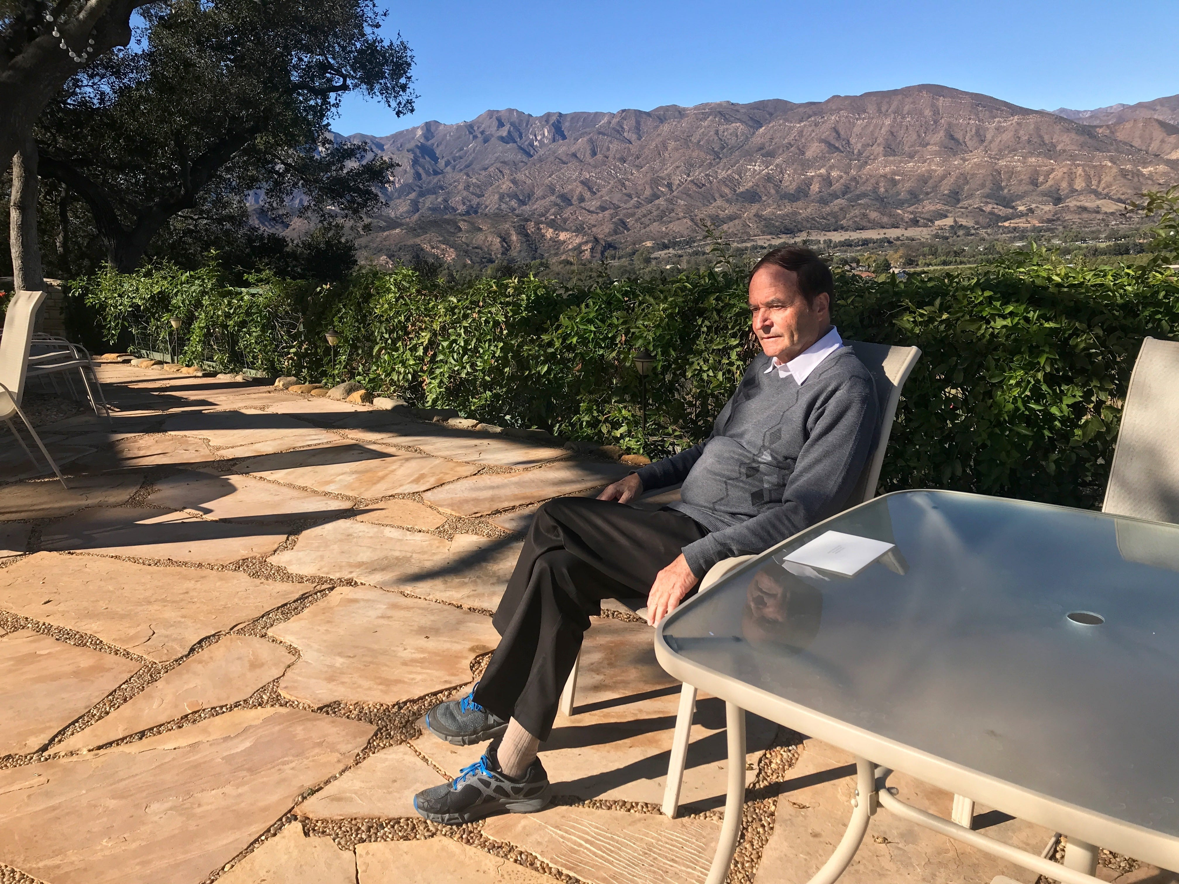 Ojai Retreat Executive Director Ulrich Brugger sits on a terrace overlooking the mountains at the lodging facility and cultural center.