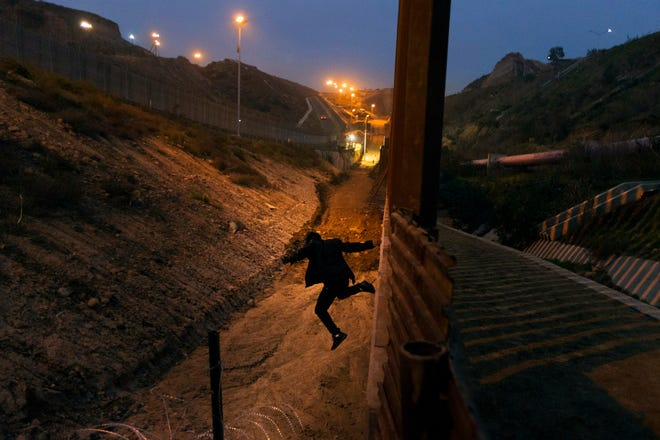 In this Dec. 21 photo, a Honduran youth jumps from the U.S. border fence in Tijuana, Mexico.  Some immigrant youth looking to start over in the United States after fleeing abusive homes are seeing their applications for green cards rejected because the Trump administration says they're too old.