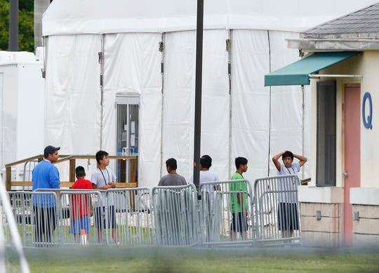 In this June 20 photo, immigrant children walk in a line outside the Homestead Temporary Shelter for Unaccompanied Children, a former Job Corps site that now houses them in Homestead, Fla.  Some immigrant youth looking to start over in the United States after fleeing abusive homes are seeing their applications for green cards rejected because the Trump administration says they're too old.