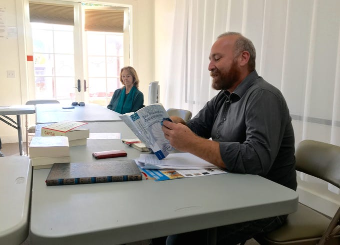 Andrew Gilman, executive director of the Agora Foundation, reads a passage from a book on philosophy during a meeting last month.