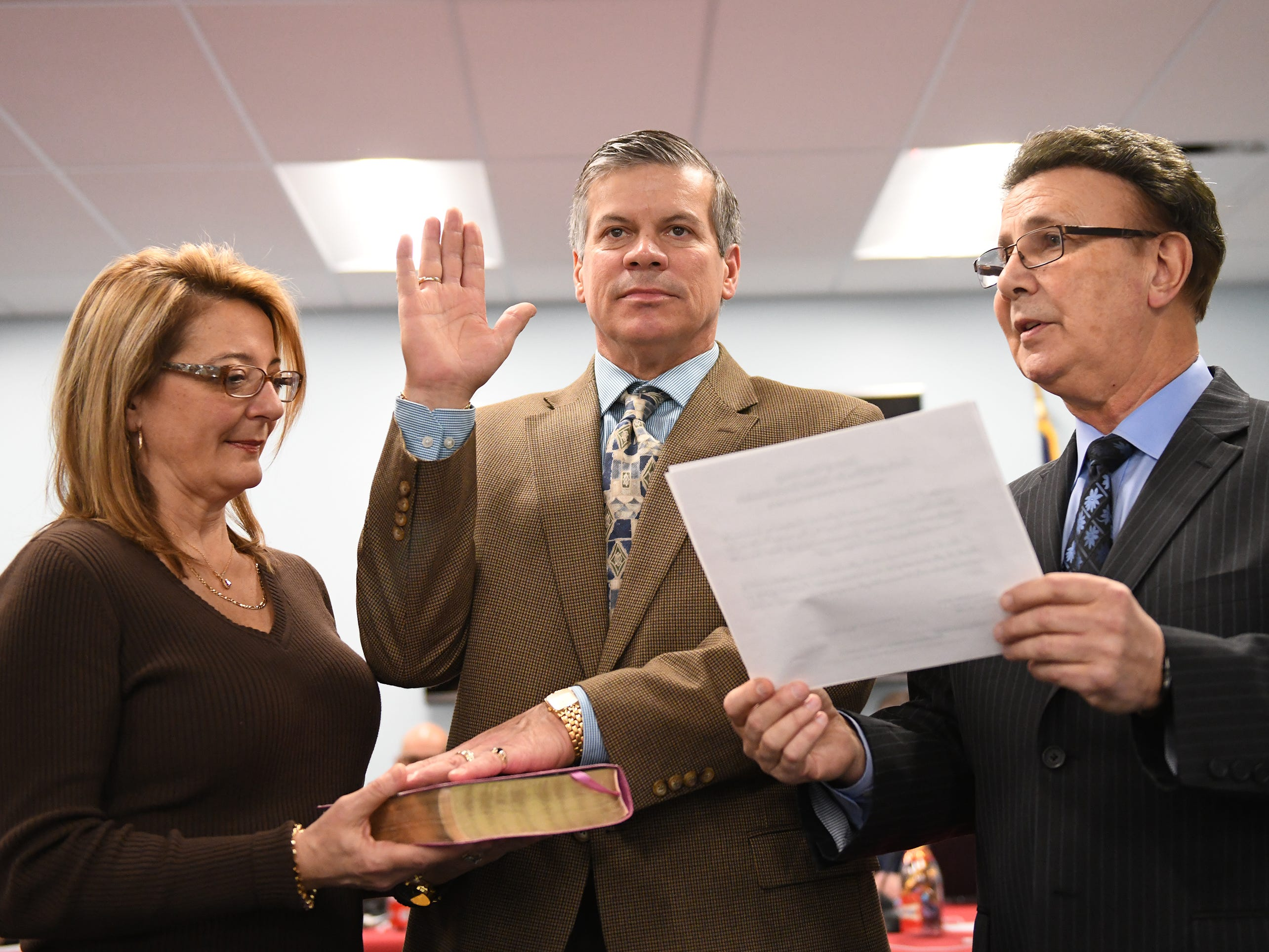 Christopher E. Jennings takes the oath of office while his wife Darla holds the bible during a Vineland Board of Education reorganization meeting on Wednesday, January 2, 2019.