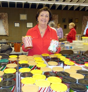 Diane Ragone, chairperson of the Woman's Club of Vineland's cookie/candy project, is surrounded by tins filled with goodies.