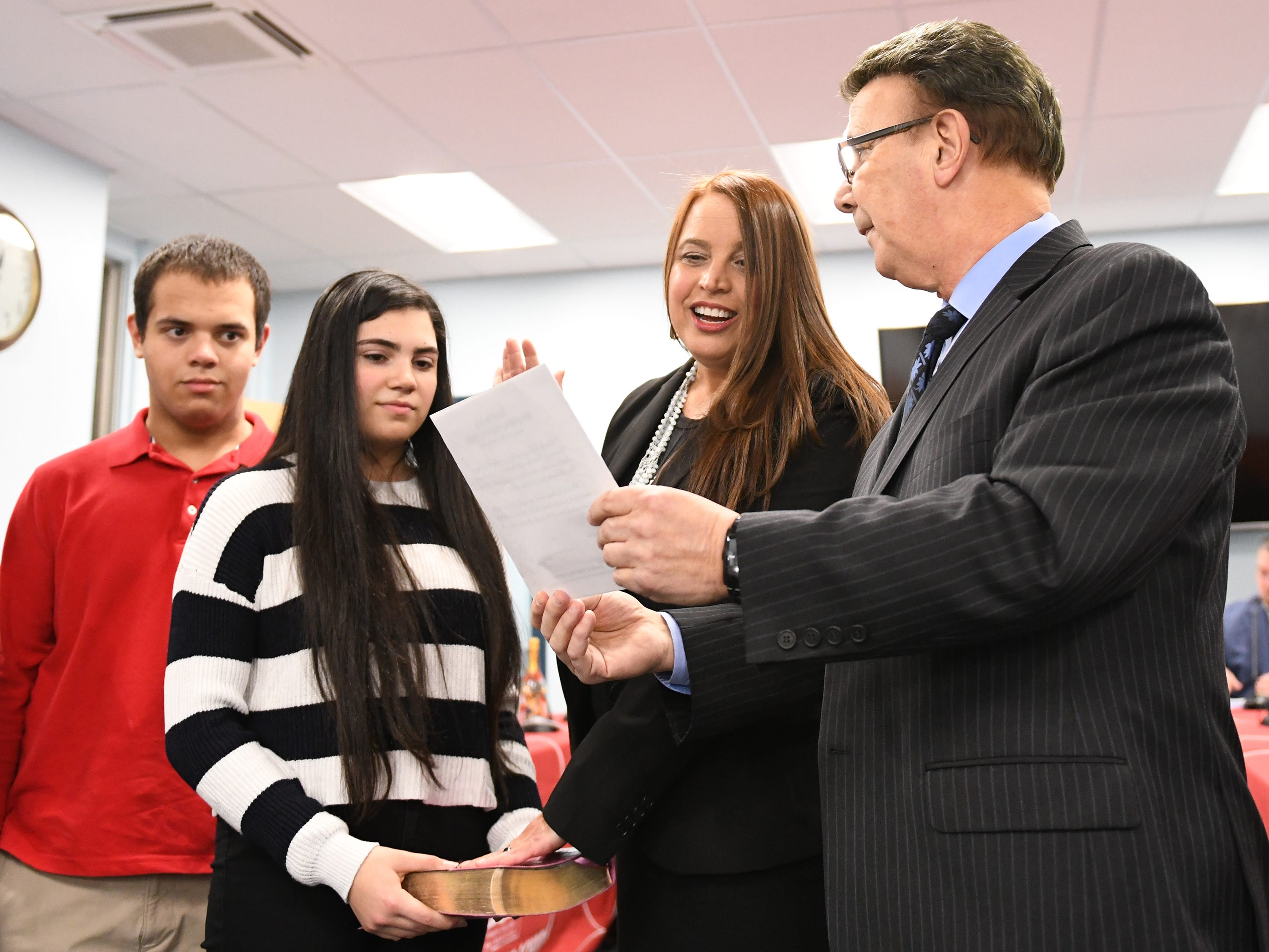 Inez Acosta takes the oath of office during a Vineland Board of Education reorganization meeting. Her daughter Lianna Vazquez holds the bible while her son Jake Cruz takes part in the ceremony. Robert DeSanto (right) holds the oath on Wednesday, January 2, 2019.
