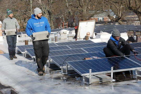 Workers from Infinity Solar of Pearl River contractors with Sun Power, install solar panels  at the Good Shepherd Church in Pearl River on Jan. 3, 2019.