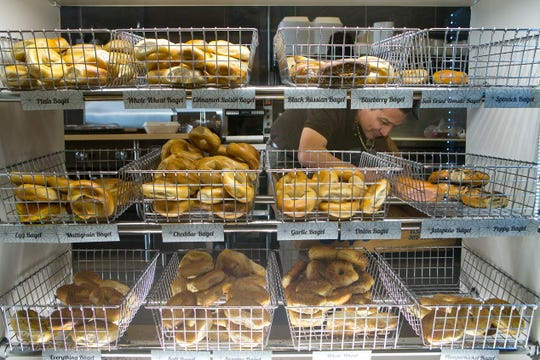 Owner Juan Duenas of The Original Hot Bagels fills the baskets with bagels which opens its doors at their third location in the Pike Creek Shopping Center.