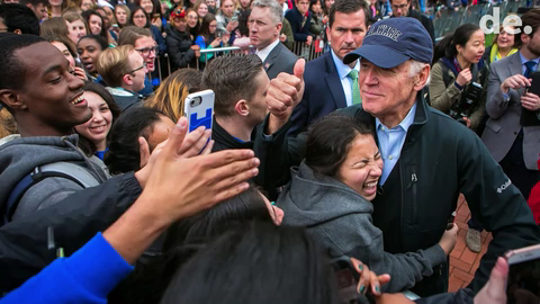 A student hugs UD alumnus and former Vice President Joe Biden who gives a thumbs up to students as he rolls through the crowd in his public return to campus in April 2017.