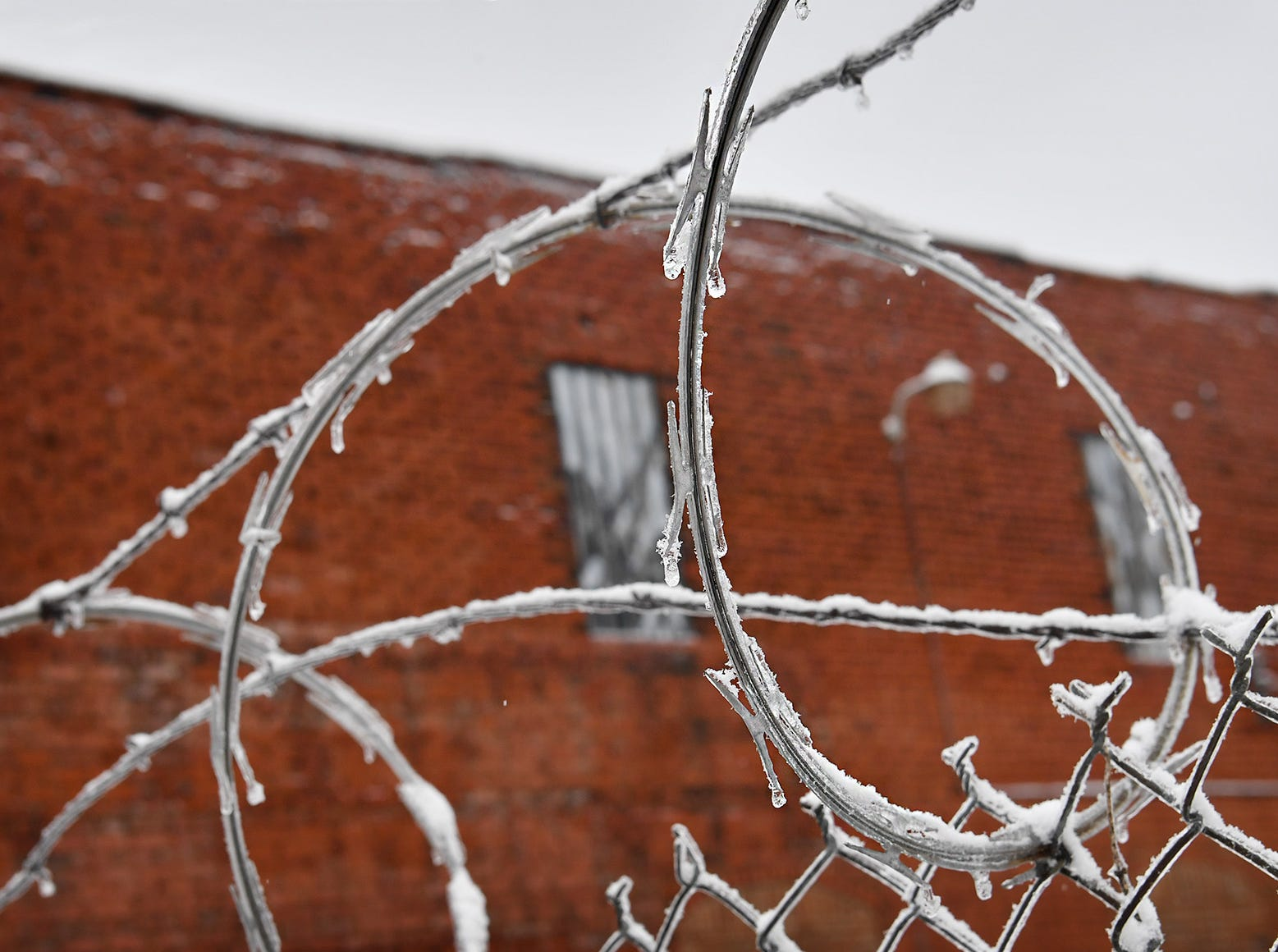 Razor wire security fencing on a downtown business covered in ice and snow Thursday.