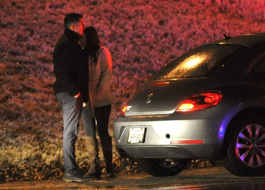 A couple hug shortly after being involved in a wreck on Kell Eastbound Access Road near Kemp Blvd., Wednesday night as winter-like area threatened the area.