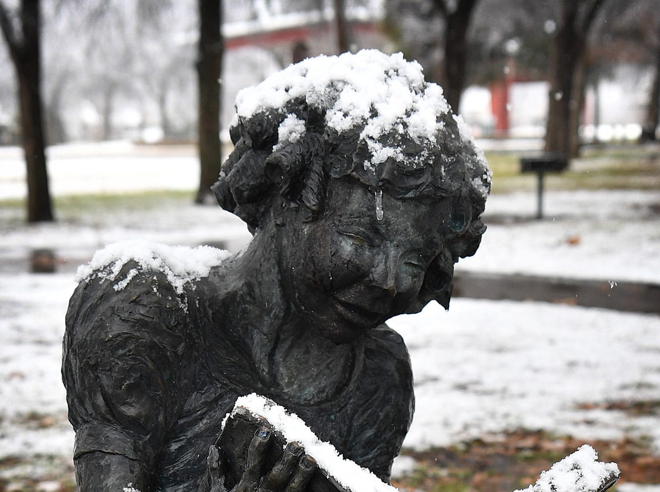A cold, bronze statue looks even colder with snow on it Thursday afternoon.