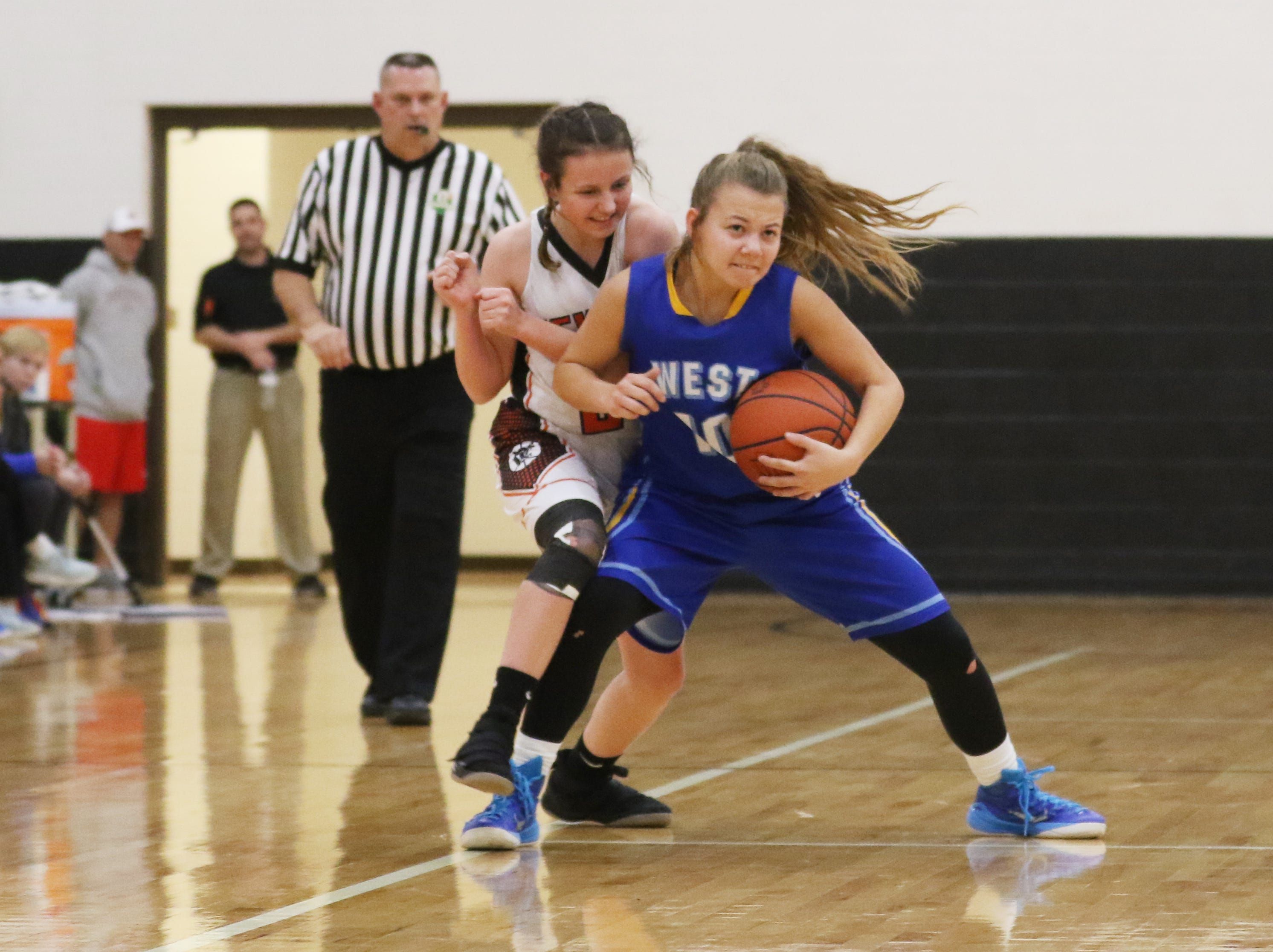 West Muskingum's Maddi Curtis tries to shed pressure from New Lexington's Lydia Stephens.