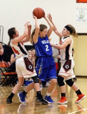 West Muskingum's Emma Allen finds herself between a pair of New Lexington defenders, Lydia Stephens (left) and Brooke Lehman during Wednesday night's matchup in New Lexington.