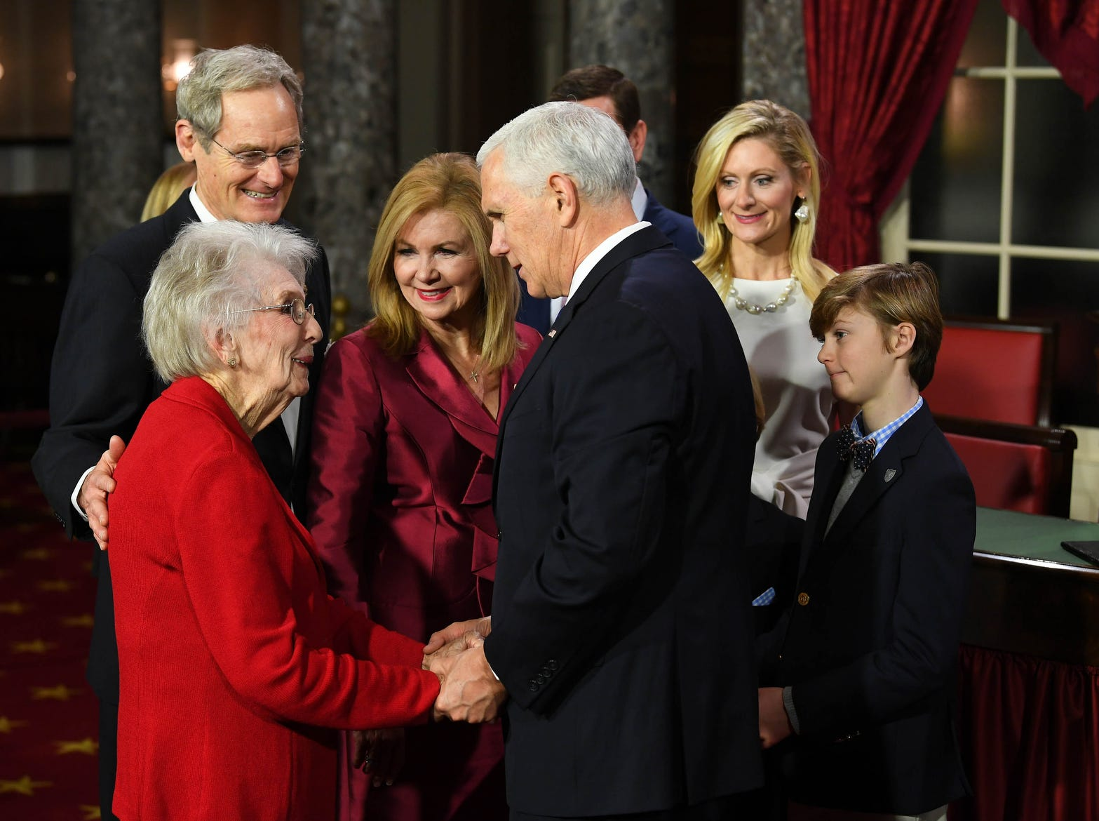ice President Mike Pence shakes the hand of Marsha Blackburn's mother Mary Jo Morgan Wedgeworth before he officiates ceremonial swearing-in of Marsha Blackburn as family members look on.