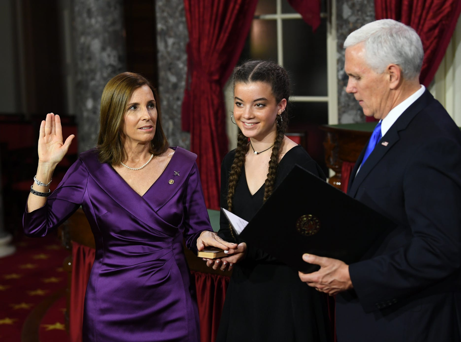 Vice President Mike Pence officiates ceremonial swearing-in of Senator Martha McSally (R-AZ) holding a Bible recovered from Pearl Harbor in the Old Senate Chambers at the U.S. Capitol.