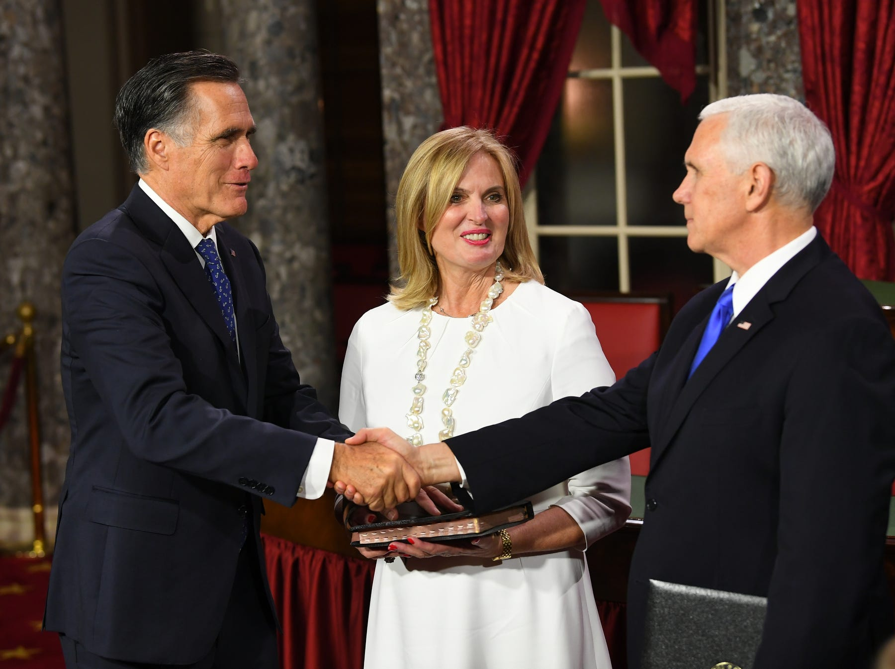 Senator Mitt Romney shakes the hand of Vice President Pence during his ceremonial swearing in as wife Ann Romney looks on.
