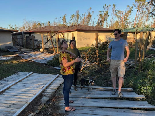 Jenneffer Azcuy (left) surveys the damage to her home after Hurricane Michael with her sister, Sasha Azcuy, and friend, James Clive.