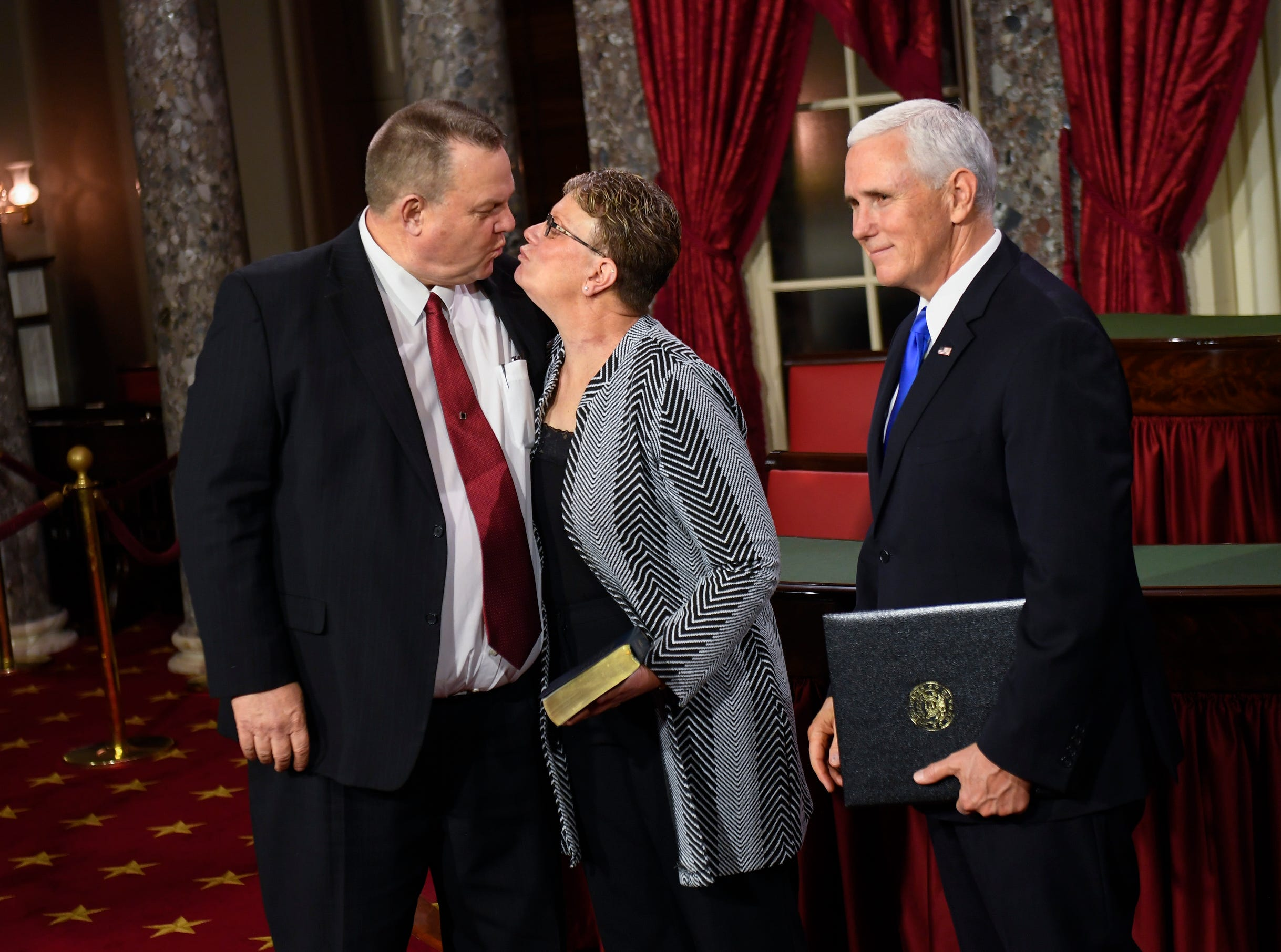 Senator Jon Tester (D-Montana) gets some love from his wife Sharla Tester, as Vice President Mike Pence the officiates swearing in ceremony.