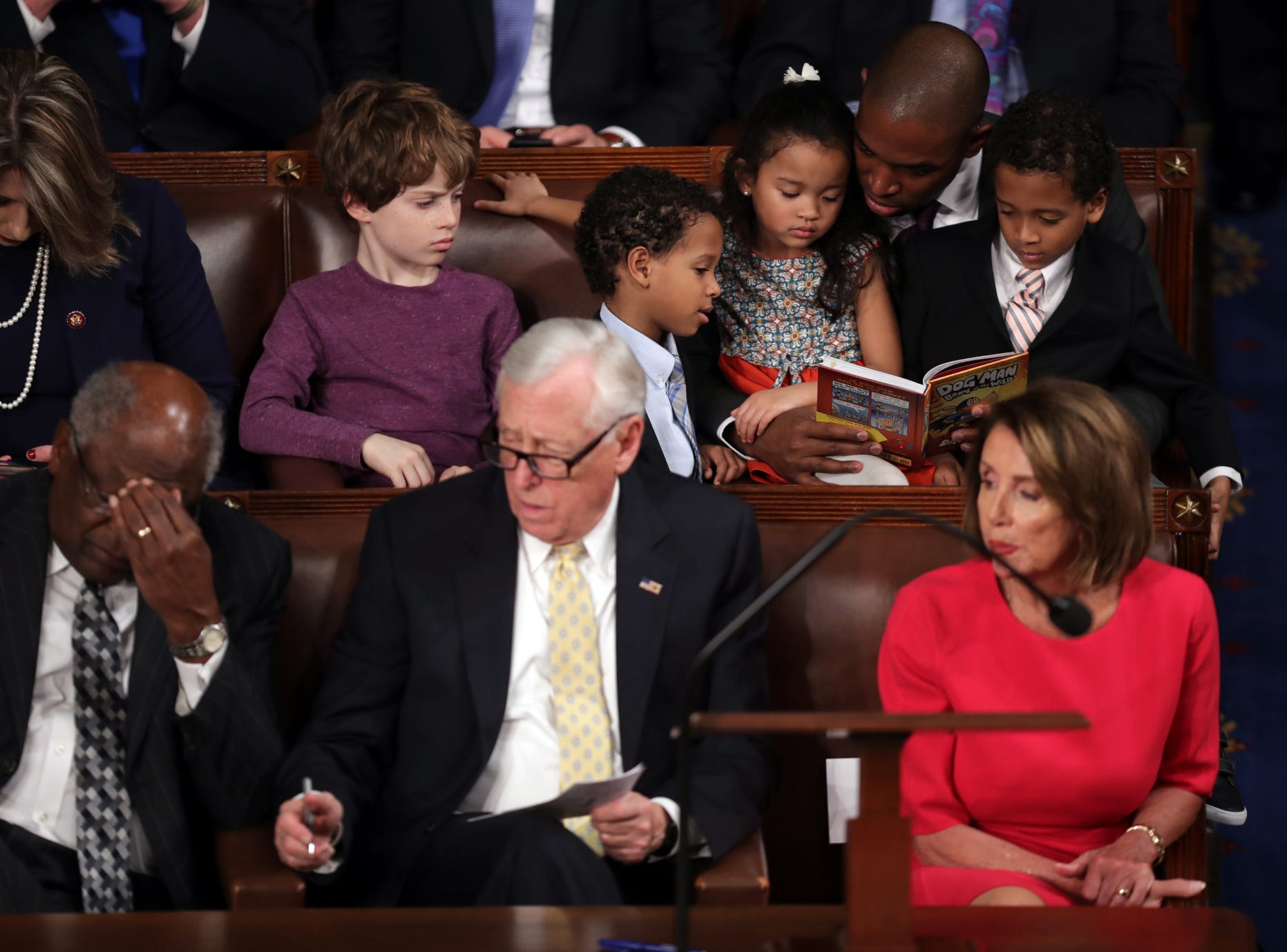 Rep-elect Antonio Delgado (D-NY) reads to children as (Bottom Row, L-R) House Minority Whip Steny Hoyer (D-MD), and Speaker-designate Rep. Nancy Pelosi (D-CA) look on.